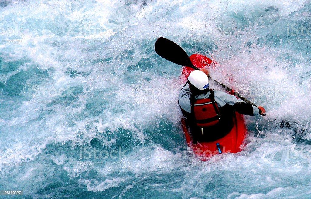 Kayaker in red kayak paddling through white water rapids  royalty-free stock photo
