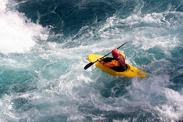kayaker maneuvers over rough waters  - extreme sporten stockfoto's en -beelden