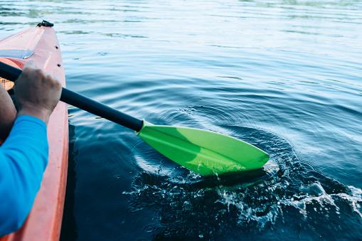 kayaker paddles across a serene lake