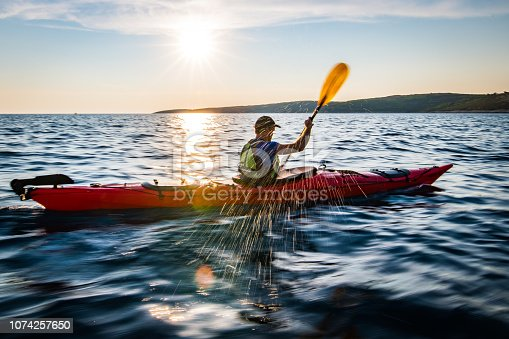 Male kayaker paddling in sea.