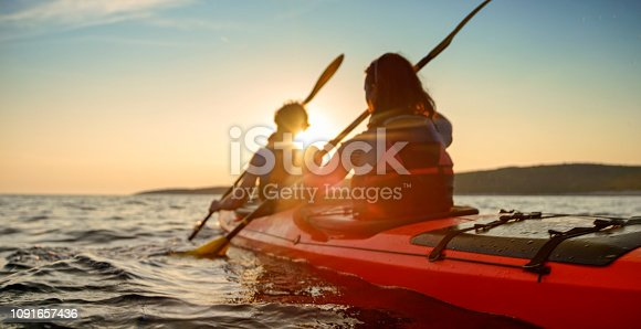 Rear view of male and female kayakers paddling in sea.