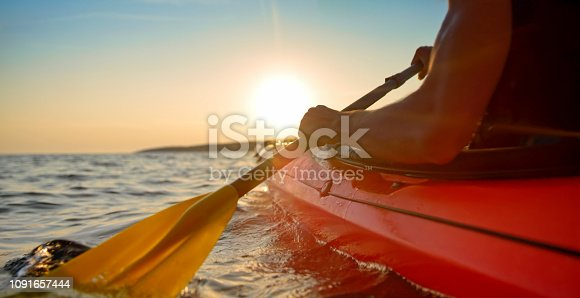 Rear view of male kayaker paddling in sea.