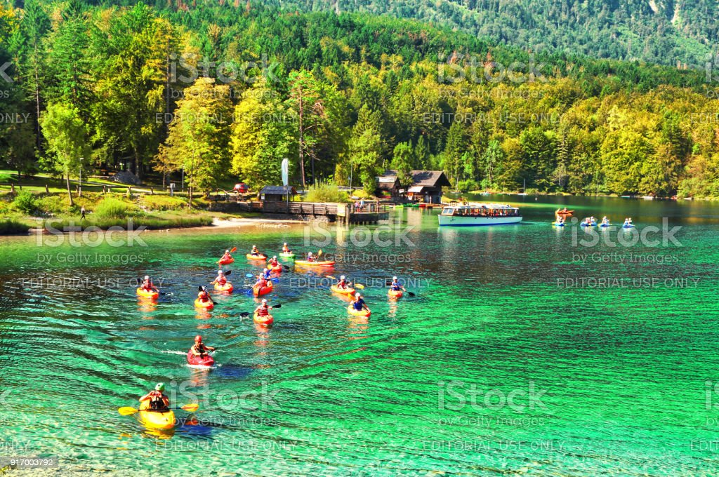 Kayakers enjoy their activities on beautiful nature of Bohinj lake with turquoise pure water with green forest stock photo