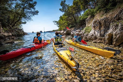 Three male kayakers paddling together in sea.