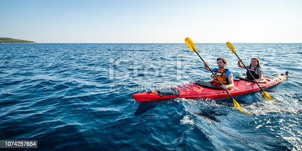 Male and female kayakers paddling together in sea.