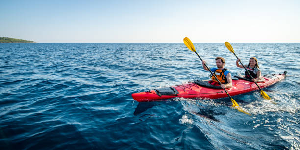 kayakers rowing together in sea - kayaking stock pictures, royalty-free photos & images