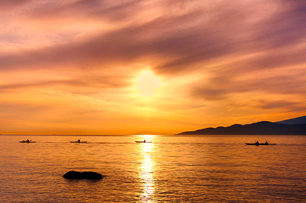 Kayakers Silhouette On Ocean During Orange Sunset stock photo