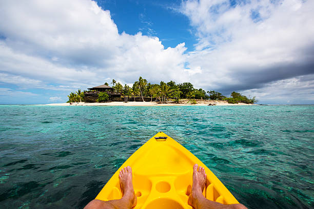 kayaking by a tropical island in fiji - fiji stock photos and pictures