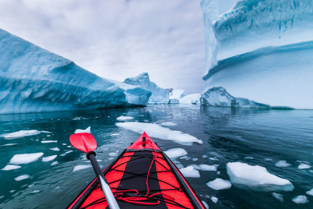 Kayaking in Antarctica between icebergs with inflatable kayak, extreme adventure in Antarctic Peninsula , beautiful pristine landscape, sea water paddling activity stock photo