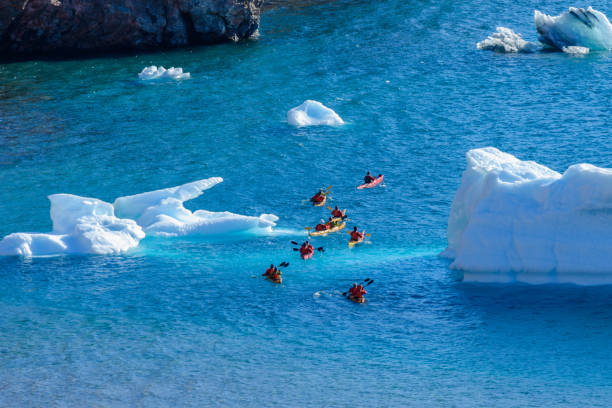 Kayaking in Arctic sea near iceberg stock photo