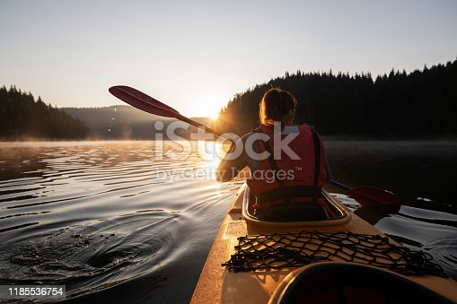 Young couple kayaking in nature before sunrise.
