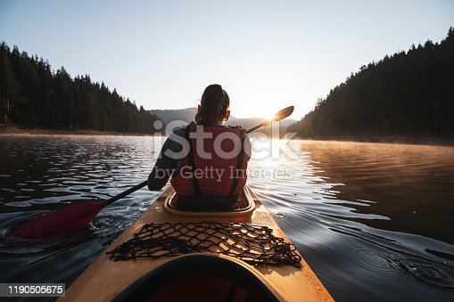 Rear view of woman kayaking in nature at sunrise.
