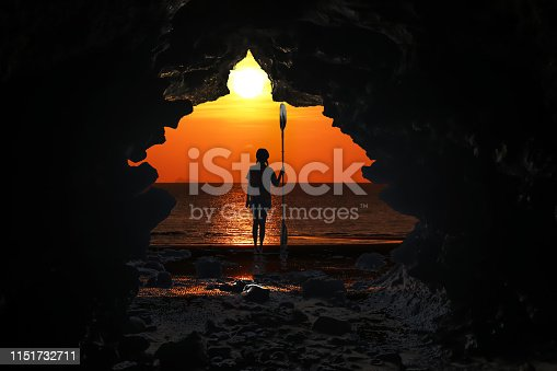 istock Kayaking in the cave, Asian girls holding the paddle stands in front of a cave by the sea at sunset 1151732711
