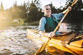 A mature adult man glides through the cool waters of Gig Harbor, Washington, a small bay in the Puget sound, paddling in a classic wood kayak.  The evening sun shines from behind, a smile on the mans face as he takes in the beauty of the great outdoors.  Horizontal image with copy space.