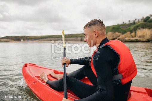 Teenage boy out at sea kayaking.