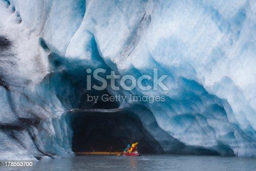 Kayaking into blue ice cave in glacier iceberg, Alaska
