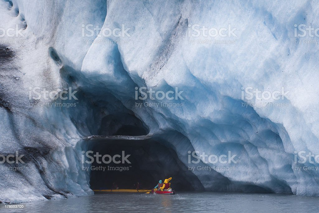 Kayaking into blue ice cave stock photo