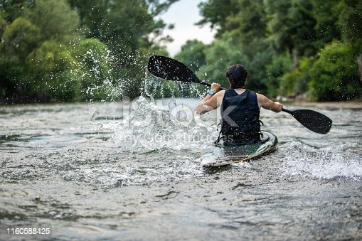 Rear view of young professional female kayaker practicing on training, rowing on river