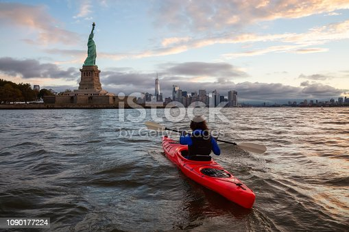 Adventurous Girl Sea Kayaking near the Statue of Liberty during a vibrant cloudy sunrise. Taken in Jersey City, New Jersey, United States.