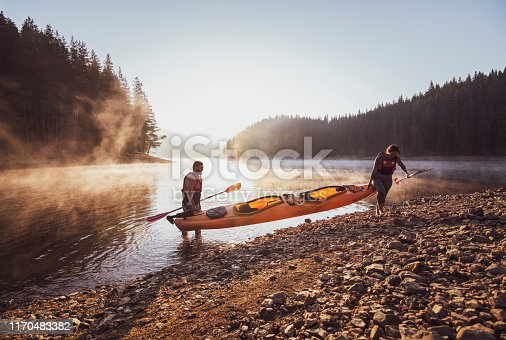 Carrying kayak and prepare to kayaking in lake at sunrise light.
