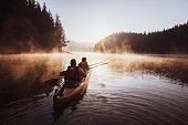 Couple rowing with kayak in lake at beautiful sunrise light.
