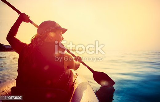Young woman is kayaking at sunset in Greece. Water splashes in the camera.
