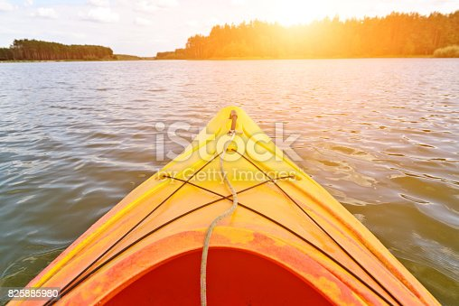 Orange kayak on the water, sun in background
