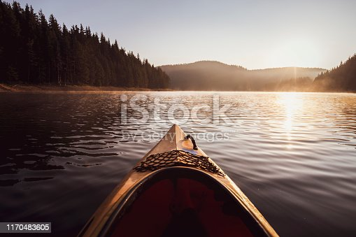 Kayaking at the sunrise light on water in reflection lake in moutnain.