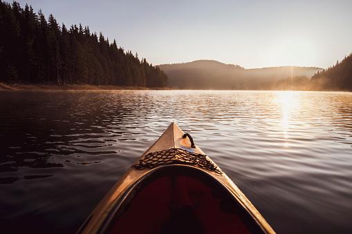 Kayaking on water in reflection lake in mountain.