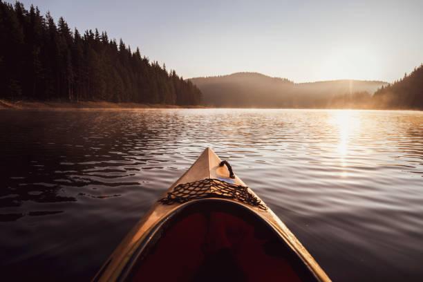 Kayaking on water in reflection lake in mountain. Kayaking at the sunrise light on water in reflection lake in moutnain. reflection lake stock pictures, royalty-free photos & images