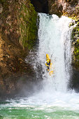 Man in yellow kayak going over a big waterfall. Extreme sports in nature. Danger on river.