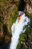 Man in red kayak going over a big waterfall. Extreme sports in nature. Danger on river.