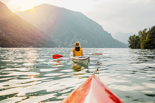 A woman from the back in the kayak with sea belt and hat