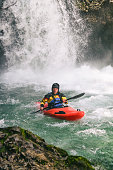 Man in red kayak in a river under a big waterfall. Extreme sports in nature. Danger on river.