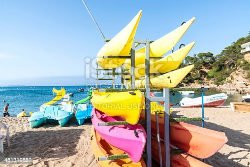 Girona, Spain - July 1, 2015: Kayaks, canoes and pedalos with slides on the beach of Sa Riera in Costa Brava, Catalonia, Spain