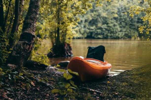 Kayaks left on a wild river shore stock photo