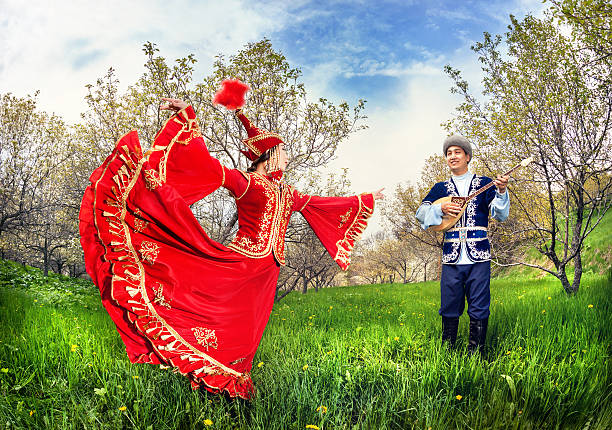 Kazakh couple in traditional costume Kazakh woman dancing in red dress and man playing dombra at Spring Blooming garden in Almaty, Kazakhstan, Central Asia kazakhstan stock pictures, royalty-free photos & images