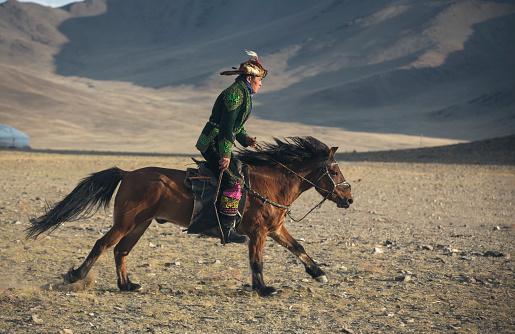 Bayan Ulgii, October 2015: kazakh eagle hunter in traditional clothing, riding a horse