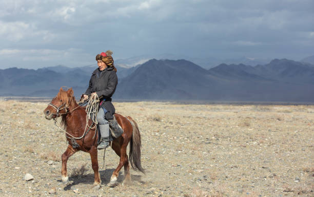 kazakh eagle hunter traveling on hgis hotse in a landscape of altai Mountains stock photo