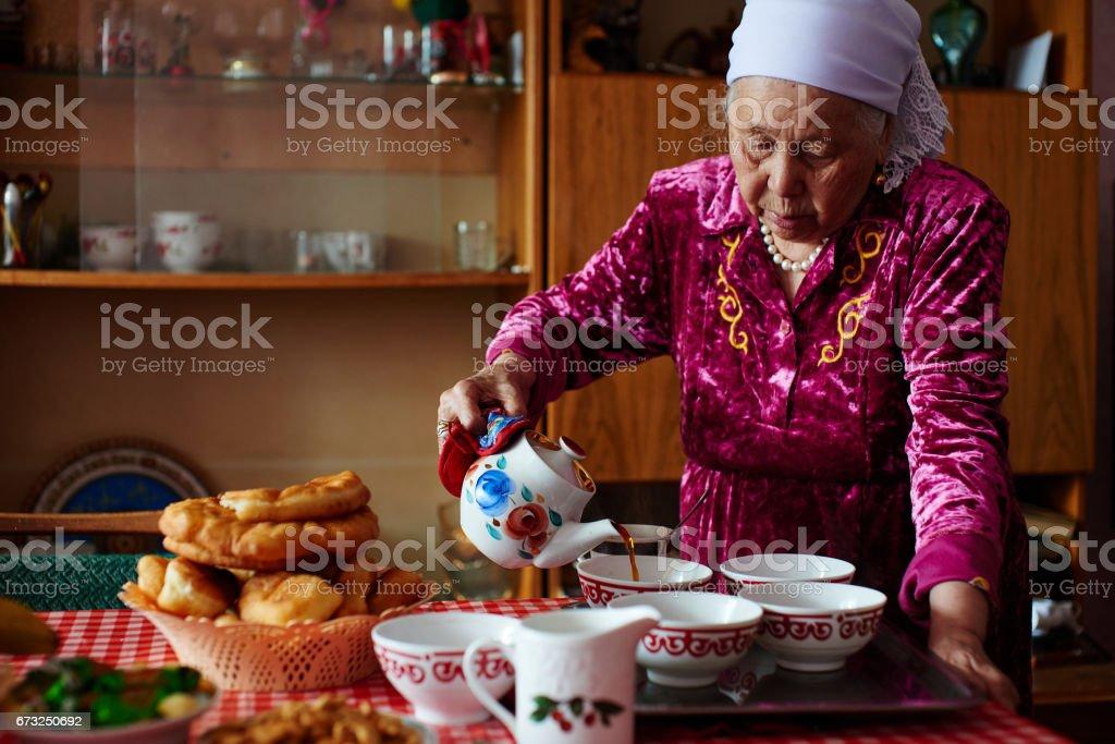 Kazakh grandma pours tea stock photo