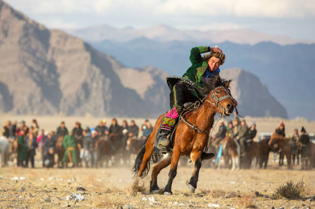 kazakh man on a horse fast speed while holding onto his hat - altai nature reserve стоковые фото и изображения