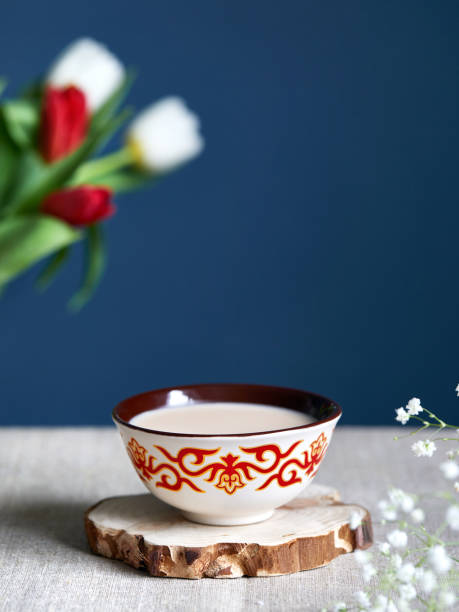 Kazakh traditional tea bowl kese with black tea and milk inside near tulips Kazakh traditional tea bowl kese with black tea and milk inside near tulips at dark blue background during Nauryz festival. muziekfestival stock pictures, royalty-free photos & images