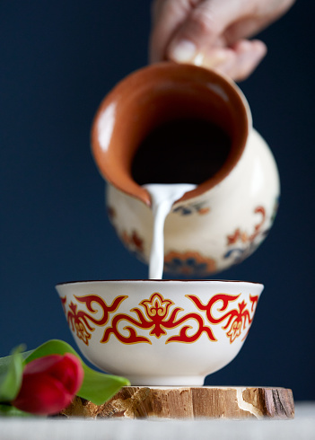 Kazakh woman pouring out milk in traditional tea bowl kese with Kazakh ornament near read tulips at dark blue background during Nauryz festival.