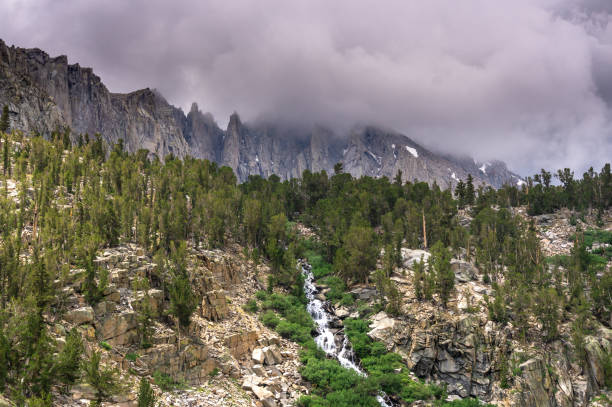 Kearsage Pass Waterfall in the High Sierra with University Peak Hidden in Cloud stock photo