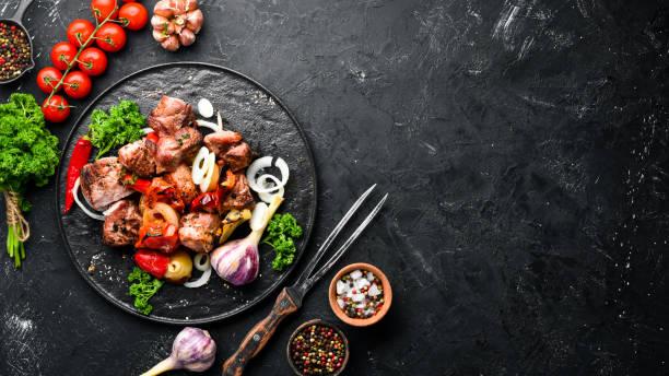 Kebab em uma placa. Carne cozida com cebolas e tomates. Churrasco. Vista superior. Espaço livre para o seu texto. Estilo rústico. - foto de acervo