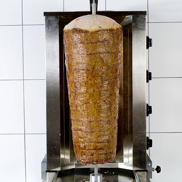 Kebab on a rod with a white tile background kebab spit roasted stock pictures, royalty-free photos & images
