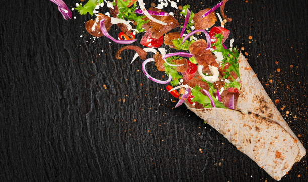 döner-sandwich mit fliegenden zutaten - veggie wraps stock-fotos und bilder