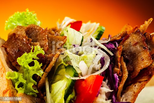 Kebabs - grilled meat and vegetables in bread on wooden background