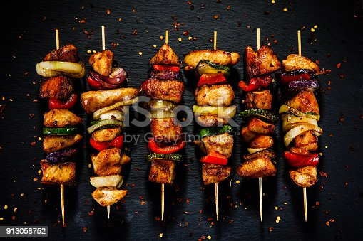 Kebabs - grilled meat and vegetables on wooden background
