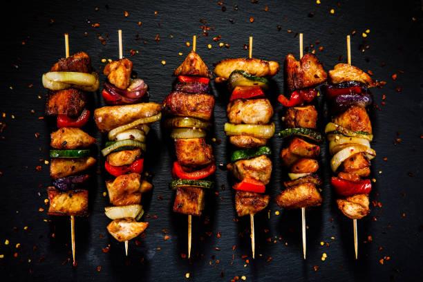 kebab - gegrilltes fleisch und gemüse auf hölzernen hintergrund - spieße grillen stock-fotos und bilder